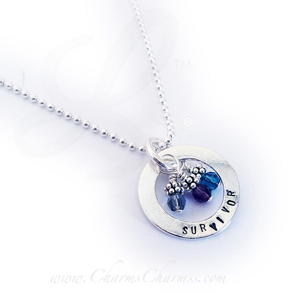 Survivor necklace shown with 3 crystals, representing Ovarian Tumors (teal), Thryoid Tumors (Purple) and Brain Tumors (grey)